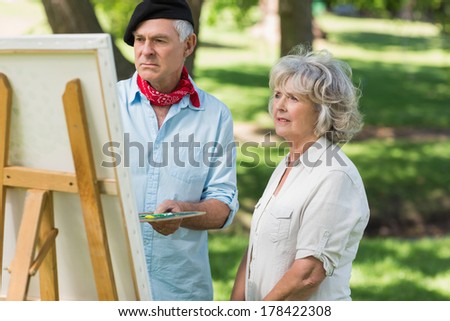 Woman watching mature man paint on canvas in the park - stock photo