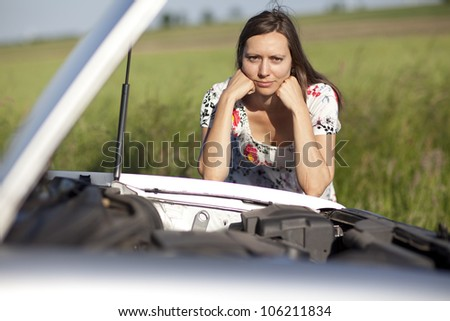 Woman watching the engine of a broken car - stock photo