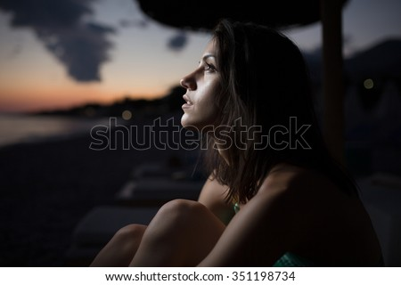 Woman watching the ocean,sea horizon with a Moon on the sky.Eclipse of the Moon.Eclipse of the sun.Stargazing,watching stars on the beach under the moonlight.Enjoying summer nights.Night sky.Sunrise - stock photo