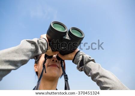 Woman watching though telescope - stock photo