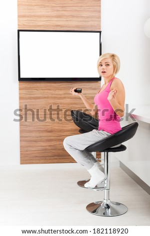 woman watching tv negative emotion scared, terrified hold remote control changing channel, shock fear girl in living room at home, isolated screen empty copy space