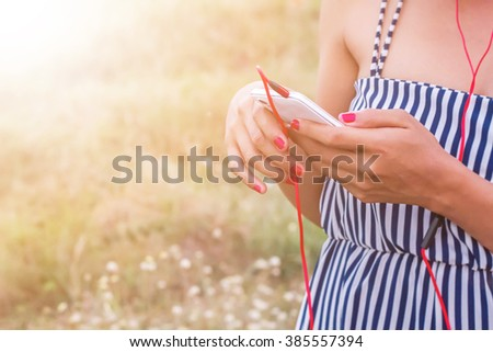 Woman watching videos in a smart phone with red earphones stand in a park  in the background - stock photo