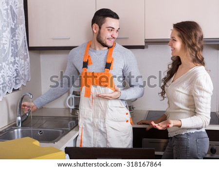 Woman watching worker repairing water lines at kitchen