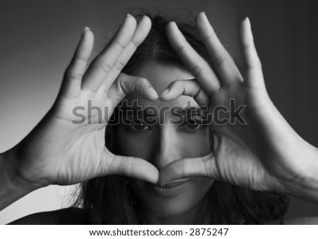 Woman watching you through the cute heart. - stock photo