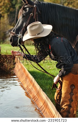 woman waters the horse