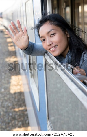 Woman waving a greeting from moving train. A passenger traveling in a moving train and looking out the window. Asian tourists waving a greeting to the open window of a moving train.