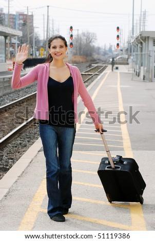 woman waving at train station - stock photo