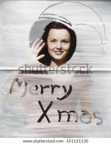 Woman waving at window with Christmas greeting - stock photo