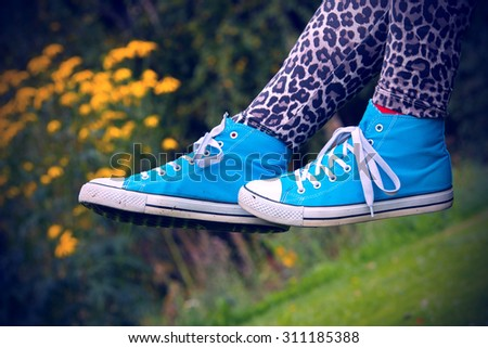 Woman waving her legs in the air in Finland. She is wearing a leopard-print pants and blue sneakers. Image includes a effect.