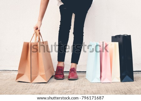 woman wear black jeans holding shopping bag on the ground