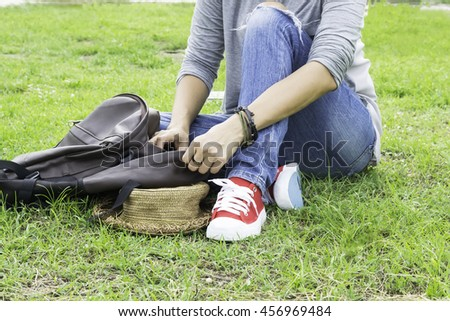 Woman wear jeans wear red shoes sitting in the grass,leisure with the bag and hat . - stock photo