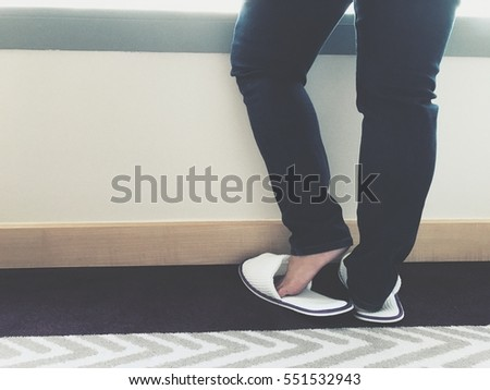 Woman wear luxury slipper shoes standing close to window relaxing with morning sun