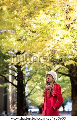 Woman wear red coat  with sunshine light and yellow ginkgo tree.