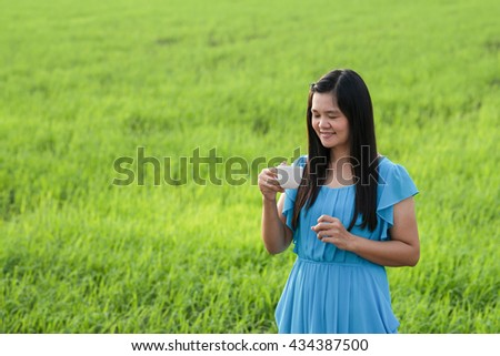Woman wearing a blue dress holding a cup coffee .