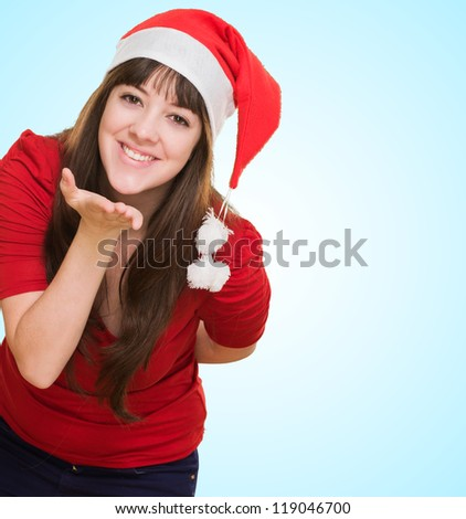 woman wearing a christmas hat and blowing a kiss against a blue background