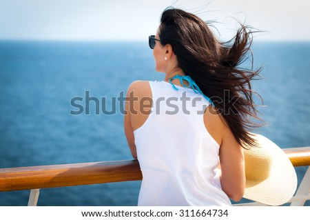 Woman wearing a floppy straw hat and a white dress standing next to the railing on a cruise ship - stock photo