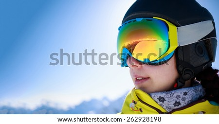Woman wearing a helmet and glasses on the background of snow mountains. - stock photo