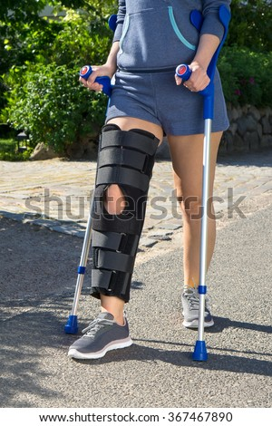 Woman wearing a leg brace with adjustable side panels to immobilize and support her knee after surgery walking on crutches outdoors on a walkway in a garden - stock photo