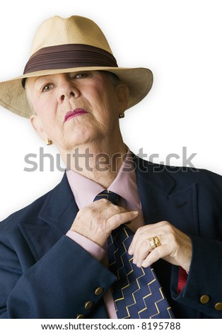 Woman wearing a man's hat and suit adjusting her tie.