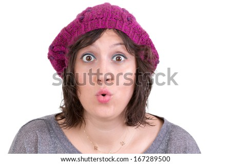 Woman wearing a purple knitted beanie reacting in amazement and wonder puckering her lips into an ooh expression with wide eyes, on white - stock photo
