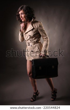 woman wearing a raincoat and holding  suitcase - stock photo