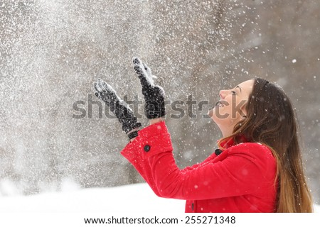 Woman wearing a red jacket throwing snow in the air in winter holidays - stock photo