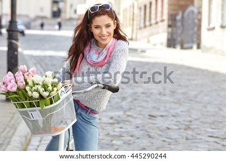 Woman wearing a spring skirt like vintage pin-up holding bicycle with some yellow flowers in the basket in old town  - stock photo