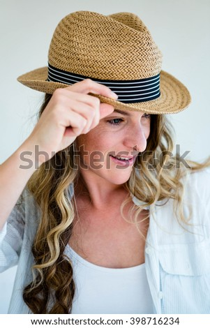 woman wearing a straw fedora, holding the rim of her hat and staring into the distance - stock photo
