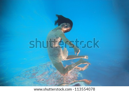 Woman wearing a white dress underwater in swimming pool - stock photo