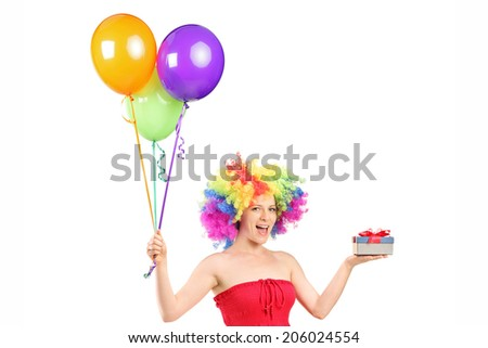 Woman wearing a wig and holding a present and a bunch of balloons isolated on white background - stock photo