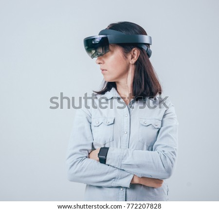 Woman wearing augmented reality goggles. White background in studio