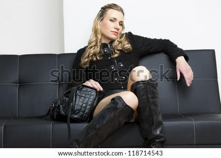 woman wearing black clothes with a handbag sitting on sofa