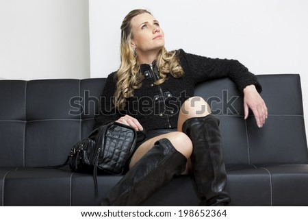 woman wearing black clothes with a handbag sitting on sofa - stock photo
