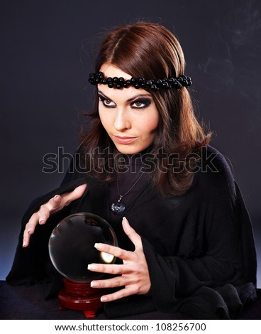 Woman wearing black with crystal ball. Fortune telling. - stock photo