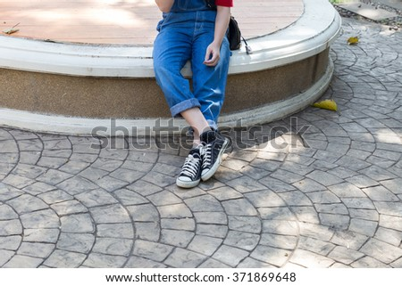 woman wearing blue jeans and black sneaker sitting and waiting - stock photo