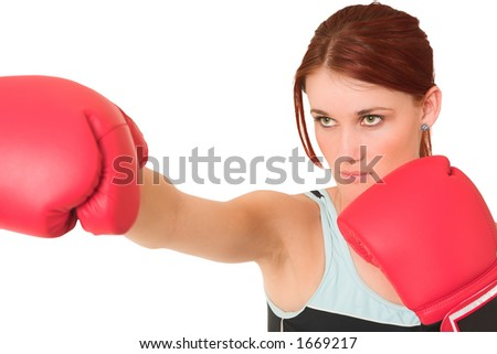 Woman wearing boxing gloves.  Looking serious. Shallow d.o.f  -  face in focus, gloves out of focus.