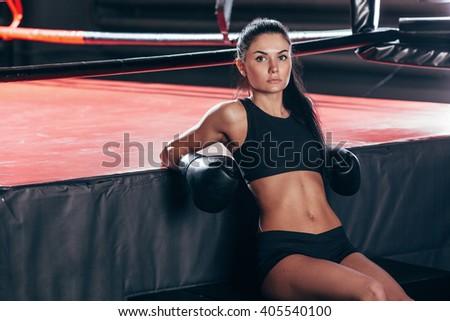 woman wearing boxing gloves sitting near ring - stock photo