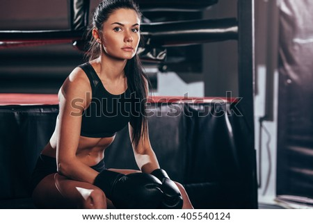 woman wearing boxing gloves sitting near ring