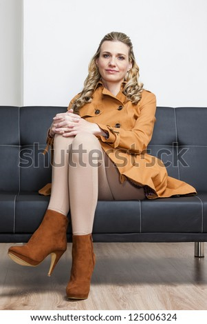 woman wearing brown coat sitting on sofa
