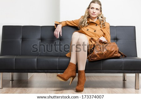 woman wearing brown coat with a handbag sitting on sofa