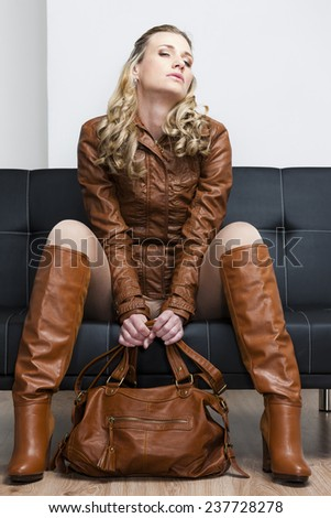 woman wearing brown jacket and boots sitting on sofa - stock photo