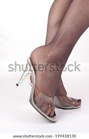 Woman wearing  clear  high heel shoes and tights over white - stock photo