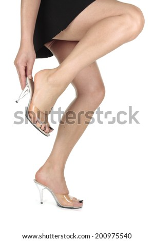 Woman wearing  clear  high heel shoes over white background - stock photo