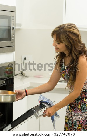 Woman wearing colorful dress in modern kitchen opening oven door holding mittens and cooking pot of metal.