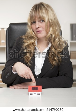 Woman Wearing Corporate Attire Pointing House Miniature on White Table, looking into Camera