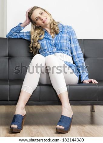 woman wearing denim clogs sitting on sofa - stock photo