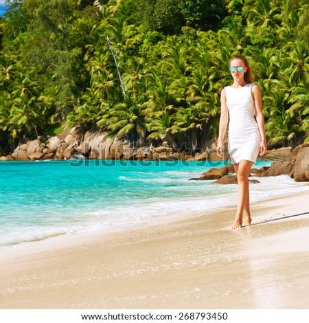 Woman wearing dress on beach Anse Intendance at Seychelles, Mahe - stock photo