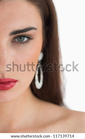 Woman wearing earrings while looking at camera and having red lips - stock photo