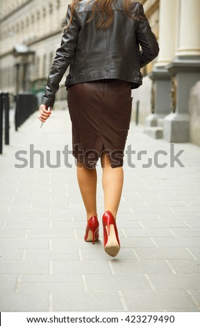 Woman wearing elegant skirt and red high heel shoes in old town. Young beautiful business sexy woman walking,urban background. Back view of a fashion shopper woman legs