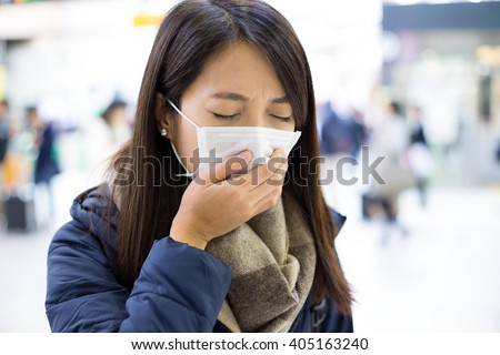 Woman wearing face mask at train station - stock photo